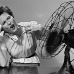 Retro photo in black and white of woman wiping sweat from her forehead while in front of a fan