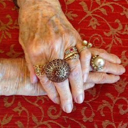 Menopause -Crone's Hands with many rings, crossed on a red patterned tablecloth